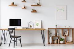 Cadeira preta na tabela com o monitor do computador no escritório domiciliário brilhante fotografia de stock