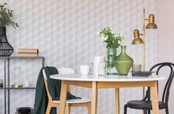Cadeira preto e branco na tabela de madeira na sala de jantar interior com flores e lâmpada do ouro Foto real fotos de stock