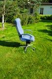 Cadeira principal do escritório da saliência no corte da grama do gramado do jardim Fotos de Stock Royalty Free