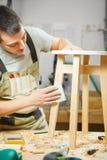Cadeira redonda polonesa do carpinteiro na oficina Carpinteiro no avental Imagem de Stock Royalty Free