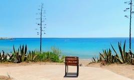 Cadeira solitária pelo mar para o abrandamento foto de stock