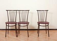 Cadeira três idêntica em seguida contra a parede Imagens de Stock Royalty Free