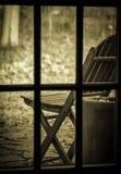 Cadeira velha através da janela imagem de stock