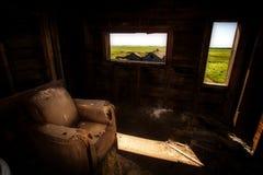 Cadeira velha do braço Rotting em cima em um sótão fotografia de stock royalty free
