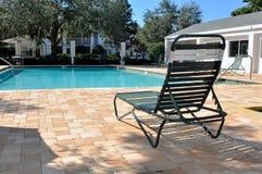 Cadeira verde da associação na frente de uma piscina Fotografia de Stock