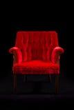 Cadeira vermelha de veludo no fundo preto Fotos de Stock Royalty Free
