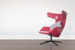 Cadeira vermelha moderna com o descanso cinzento no assoalho de madeira Imagem de Stock