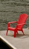 Cadeira vermelha por Água Fotos de Stock Royalty Free