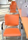 Cadeiras alaranjadas sobre um desktop coletivo Salão do serviço ao cliente Imagens de Stock Royalty Free