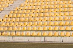 Cadeiras amarelas no campo de futebol Fotos de Stock