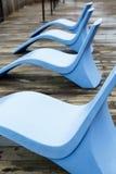 Cadeiras azuis curvadas no cais Imagens de Stock Royalty Free