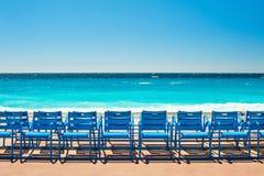 Cadeiras azuis em Promenade des Anglais em agradável, França imagem de stock