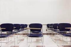 Cadeiras azuis em uma sala de aula Imagens de Stock Royalty Free