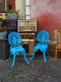 Cadeiras azuis, potenciômetros de flor e rádios velhos em um café em uma rua em Sibiu imagens de stock