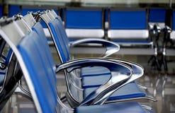 Cadeiras azuis vazias na área de espera no terminal fotografia de stock