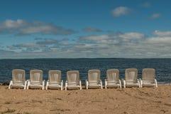 Cadeiras brancas alinhadas em um arenoso lakeshore Imagens de Stock