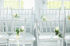 Cadeiras brancas com flores para uma cerimônia de casamento Fotos de Stock