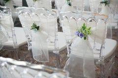 Cadeiras brancas com flores para uma cerimônia de casamento Fotografia de Stock Royalty Free