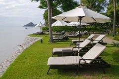 Cadeiras brancas com o parasol perto da praia fotos de stock