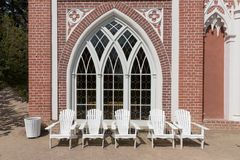 Cadeiras brancas a descansar na frente da casa de campo fotos de stock