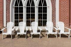 Cadeiras brancas a descansar na frente da casa de campo foto de stock