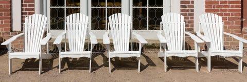 Cadeiras brancas a descansar na frente da casa de campo imagens de stock