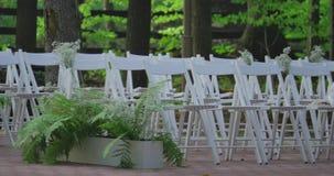 Cadeiras brancas do casamento com flores Ao ar livre cerimónia de casamento Casamento estabelecido no jardim filme
