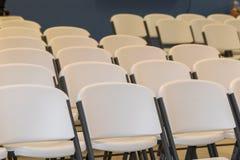 Cadeiras brancas nas fileiras foto de stock