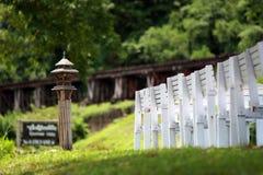 Cadeiras brancas no monte na frente da estrada de ferro de Kwai do rio Imagens de Stock Royalty Free
