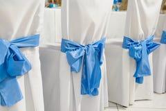 Cadeiras com tampas brancas e curva azul fotografia de stock