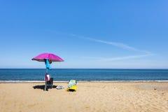 Cadeiras cor-de-rosa do guarda-chuva e de plataforma na praia na frente do oceano, Sardinia, Itália Fotos de Stock
