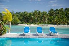 Cadeiras da sala de estar do Poolside em uma praia Foto de Stock Royalty Free