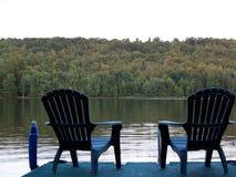 Cadeiras da serenidade no lago Fotos de Stock Royalty Free