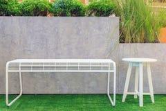 Cadeiras de aço brancas e cadeiras de madeira na grama e no cla artificiais Fotos de Stock Royalty Free