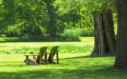 Cadeiras de Adirondack em um ajuste do país Foto de Stock
