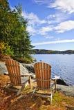 Cadeiras de Adirondack na costa do lago Imagens de Stock
