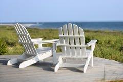 Cadeiras de Adirondack que negligenciam a praia. Foto de Stock