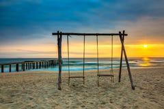 Cadeiras de balanço na praia no nascer do sol fotografia de stock royalty free