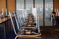 Cadeiras de cabeça para baixo na tabela Foto de Stock Royalty Free