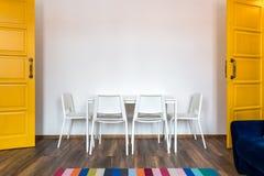 Cadeiras de madeira brancas com uma tabela na perspectiva de uma parede branca no interior com portas amarelas fotos de stock royalty free