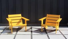 Cadeiras de madeira brilhantes nos grandes Pavers de pedra, no século ultra moderno ou meados de modernos fotografia de stock