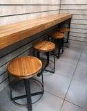 Cadeiras de madeira e contadores de madeira no café imagens de stock royalty free