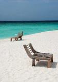 Cadeiras de madeira em uma praia Fotos de Stock Royalty Free