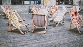Cadeiras de plataforma coloridas fora Estada no ar fresco Conforto e vadios do sol na cidade Foco raso Fotografia de Stock