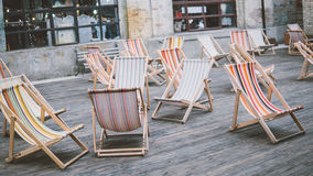 Cadeiras de plataforma coloridas fora Estada no ar fresco Conforto e vadios do sol na cidade Foco raso Fotografia de Stock Royalty Free
