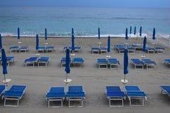 Cadeiras de plataforma e guarda-chuvas na frente do mar Imagens de Stock Royalty Free