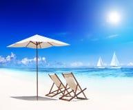Cadeiras de plataforma na praia com vista de barcos de vela imagens de stock