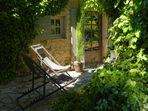 Cadeiras de plataforma no pátio no jardim Fotografia de Stock