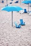 Cadeiras de plataforma plásticas azuis e guarda-chuva plástico ciano nas areias de uma praia imagens de stock royalty free
