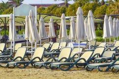 Cadeiras de plataforma vazias e guarda-chuvas fechados em um Sandy Beach imagens de stock royalty free